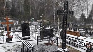 Простой мемориальный комплекс с металлическим крестом и небольшими элементами ограждения