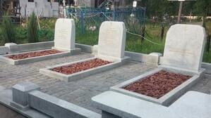 Невысокий мемориальный комплекс из светлого гранита на большом месте захоронения
